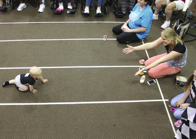 Anna Bolton | Greene County News Bodie Roman, 9 months, crawls to his mom at the finish line Aug. 1 during the Diaper Derby at the Greene County Fair. Rules allowed one parent or guardian to coax his or her crawling baby with a toy or bottle from the finish line.