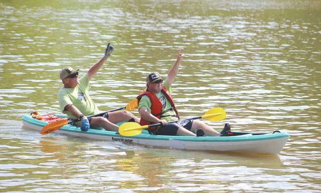 Dylan Chard (front) and his father, Mike, point to Heaven as they finish the 5.2-mile K2 Men's Paddling competition, July 28 in Fairport Harbor. The Chards repeated as state champions at the meet.