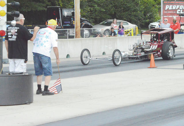 Like they used to do in the early days of drag racing, Gathering of the Geezers organizer Ed Crowder prepares to raise the flag to signal the start of a Grandpa Eliminator class race, Aug. 18 at Kil-Kare Dragway. Brookville's Rick Lawson (shown, far lane) was a runner up in the class.