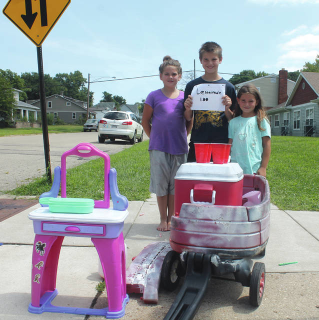Anna Bolton | Greene County News Siblings Neveah Colquhoun, 9, Braiden Mattox, 12, and Brianna Caplinger, 6, sell pink lemonade from their neighborhood lemonade stand at the corner of North Columbus and East Market Street Aug. 9. The trio is selling $1 lemonade and candy every day until school starts.