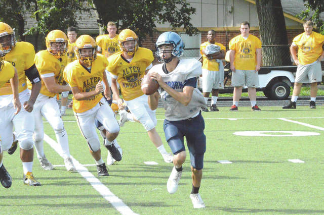 A Fairborn quarterback looks for an open receiver downfield as a wave of Alter Knights follow in pursuit, Aug. 7 in Kettering. Fairborn was involved in a tri-scrimmage with 2017 playoff teams Cincinnati Taft and host Kettering Alter.