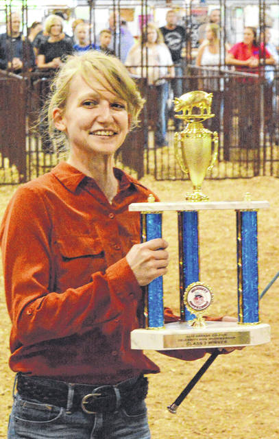 John Bombatch | Greene County News Whitney Vickers proudly holds her first-place trophy after winning the second group of the Celebrity Swine Showmanship contest Aug. 1 at the Greene County Fair.