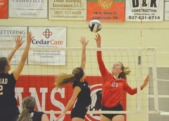 Cedarville's Abigail Sheridan tips a shot over a pair of Triad defenders during Thursday's Ohio Heritage Conference girls high school volleyball match in Cedarville. Sheridan led the Indians hitters with 14 kills.
