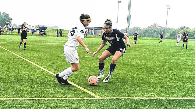 Lyndsey Smith (right) puts the defensive pressure on her Malone opponent, Sept. 8 in Xenia.