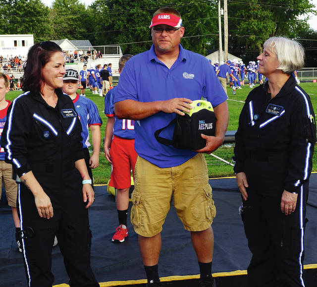 Barb Slone | Greene County News Anna Houser and Linda Irvin, representatives from Premier Health, present an automatic external defibrillator to youth football coach Brian Payton.