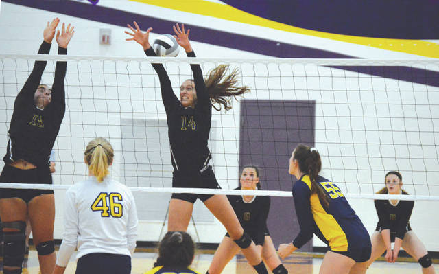 Kira Merkle (14) and teammate Sydney Krane go up to try and block an Oakwood kill, Sept. 6 in a girls high school volleyball match at Bellbrook High School. Merkle had a match-best 12 kills to go with three aces in the Golden Eagles win.