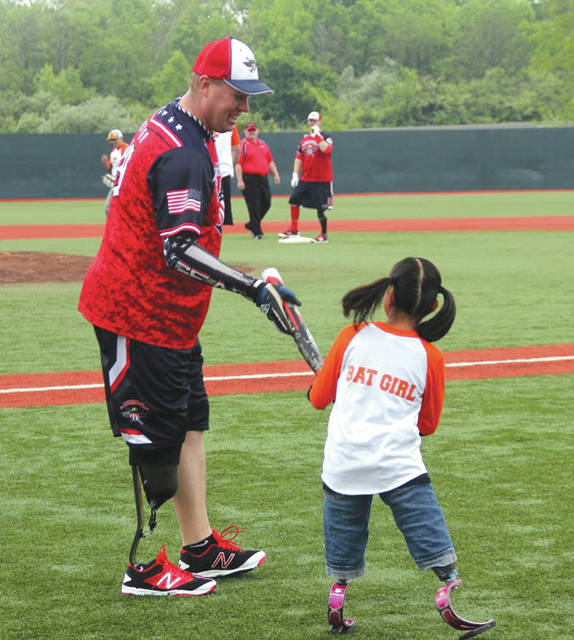 A member of the nationally known Wounded Warrior Amputee Softball Team hands his bat to a guest amputee bat girl during a recent charity softball game. The Wounded Warrior team will play a pair of exhibition games Saturday, Oct. 13 at Wright State University's Nischwitz Stadium.