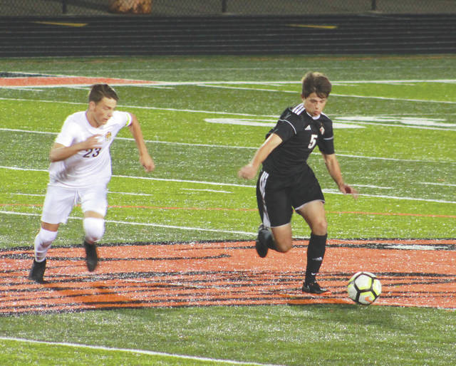 Beavercreek Junior Gavin Coots dribbles the ball through center field as Centerville junior midfielder Ryan Forino defends, Oct. 9 at Beavercreek High. Centerville won the game, 2-1, to claim the Greater Western Ohio Conference's National East title.