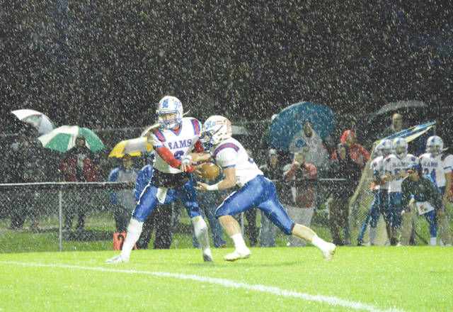 Greeneview quarterback Nick Clevenger hands off to Clay Payton in the pouring rain, Friday, Oct.12 at Cedarville High School. The Rams won the contest, 52-8.