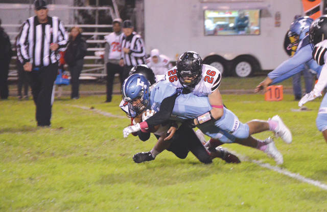 Fairborn senior running back Trae Long dives for extra yardage, and brings a pair of West Carrollton defenders with him, in the first half of Friday's Skyhawks win, Oct. 19 at Memorial Stadium.