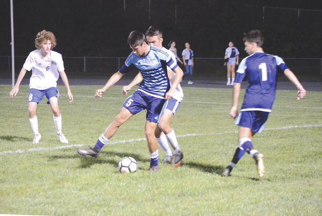 Guarded heavily by Xenia's Elijah Cushman and Logan Higgins, Fairborn senior Joe Nickel (5) passes the ball to Skyhawks senior midfielder Troy Herald, during the first half of Tuesday night's boys high school soccer match in Fairborn. Herald returned the favor in the second half, assisting on two Nickel scores in the Skyhawks' 6-2 win.