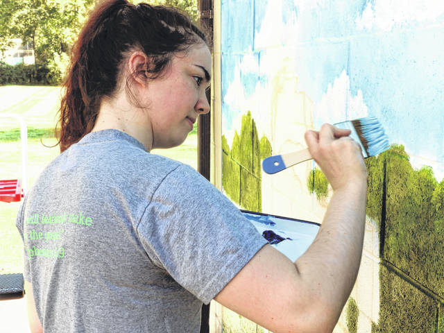 Submitted photos Elizabeth Patterson works on creating the mural on GCP&T's Spring Lakes Park Bait House in Bellbrook.