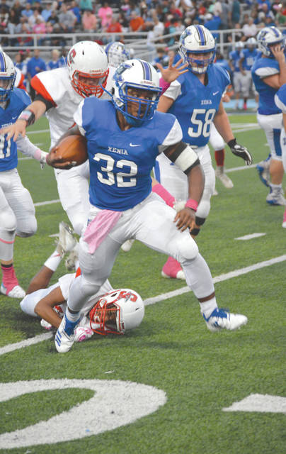 Xenia senior running back Sincere Wells (32) breaks out of a Stebbins tackle on his way to a first-half gain, Oct. 5, at Doug Adams Stadium. Wells scored four touchdowns and rushed for a game-best 130 yards in Xenia's 52-10 win.