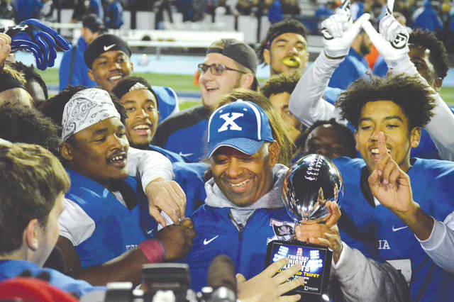 Xenia head football coach Trace Smitherman celebrates with Buccaneers running back Sincere Wells (left) and the rest of the team after being presented with the Thursday Night Lights trophy for defeating Fairborn, Oct. 25, at Doug Adams Stadium.