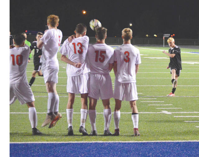 Junior midfielder Pete Schneider launches a direct kick over a wall of Troy defenders for a score, Monday, Oct. 22 at Doug Adams Stadium in Xenia. Beavercreek defeated Troy 6-1 in the Dayton 3 Bracket sectional tournament final to advance.
