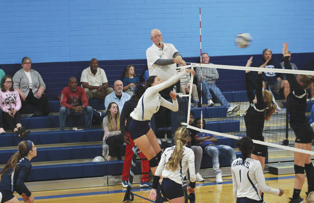 Fairborn junior LeeAnn Williams (6) hits the ball just over Xenia's block attempt to score a kill in the third set, Oct. 11 at Fairborn High School.