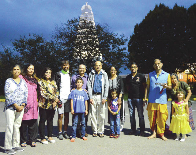 John Bombatch | Greene County News With the Hindu Temple of Dayton in the background, Dnyaneshwar Yeotkar (fourth from left) poses with Temple members upon arriving Oct. 4, in Beavercreek during a stop along his World Bicycle March for Peace & Friendship. Yeotkar is in the second of a four-year bicycling journey around the world.