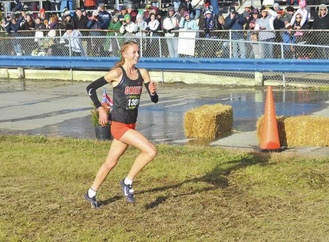 A lot of mud, wind and some frigid temperatures couldn't keep Beavercreek's Taylor Ewert from smiling as she won the Division I girls race, Nov. 10 at the state cross country championships at National Trail Raceway in Hebron.