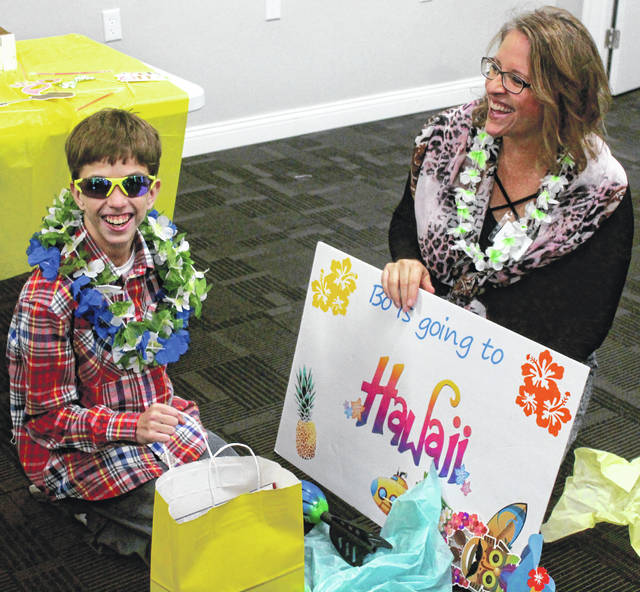 Anna Bolton | Greene County News Bo Porter, 12, of Xenia, laughs as he tries on a new pair of sunglasses next to his mom, Katey Porter, at his Make-A-Wish reveal party Dec. 9 at Life House Church in Beavercreek.