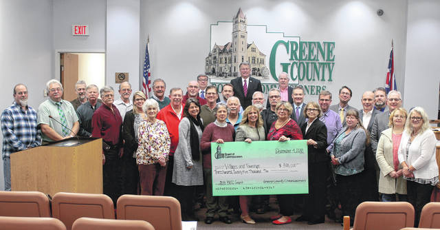 Anna Bolton | Greene County News Greene County Commissioners Bob Glaser, Tom Koogler and Alan Anderson present checks to village and township officials Dec. 4 as part of a new Department of Development grant program.