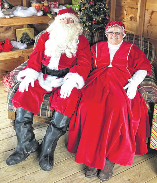 Santa and Mrs. Claus wait for kids to visit them during Hometown Christmas.