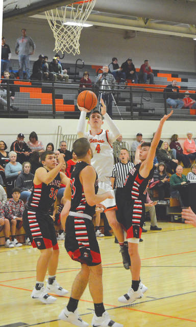 Brayden Walther, of Beavercreek, goes up for a shot between a trio of Tecumseh Arrows defenders, Dec. 22 in a boys high school basketball game at Beavercreek High School.