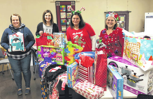 Photos courtesy FVPC Family Violence Prevention Center of Greene County staff members collect gifts from various local donors. Families at the safe house will soon open the holiday gifts.