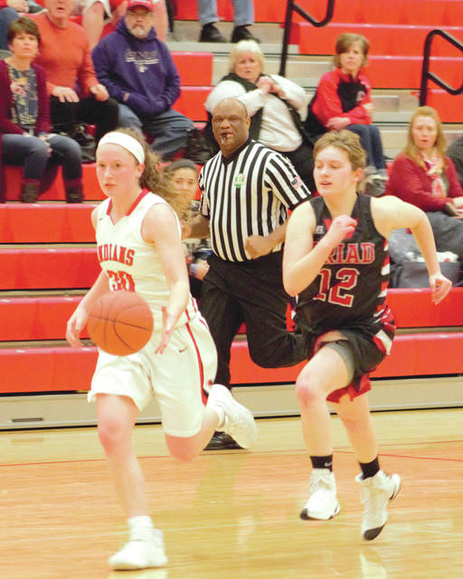 Triad's Bailey Perry (12) gives chase as Cedarville senior Maggie Coe drives in for an easy layup, Jan. 24, against Triad at Cedarville High School.