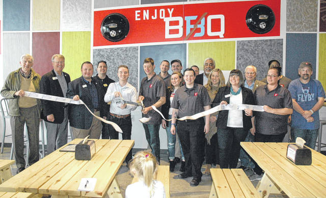 Scott Halasz | Greene County News The staff of Flyby BBQ and dignitaries from Beavercreek and Greene County cut the ribbon to signify the opening of the new restaurant at The Mall at Fairfield Commons.