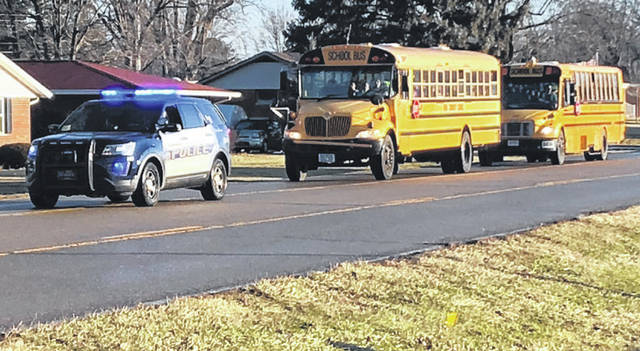 Scott Halasz | Greene County News A Xenia police car escorts school buses full of students from the high school to a nearby church Feb. 4. The school was locked down and eventually closed for the day because of a threat made by a student.