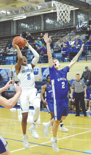 Fairborn's Shaunn Monroe (3) goes in for a score against Miamisburg sophomore Luke Copsey, in the first half of Tuesday's Feb. 12 boys high school basketball game at the Baker Memorial Fieldhouse in Fairborn. Monroe led all scorers with 27 points in the loss to the Vikings.