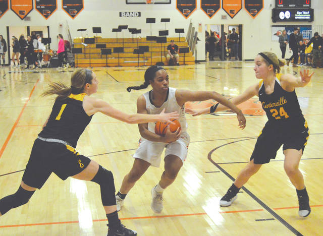 Beavercreek senior forward Kirsten Williams is double-teamed by Centerville's Alexis Hutchinson (1) and Kelsey George (24) in the first half of Wednesday's girls high school basketball game at Beavercreek High School.