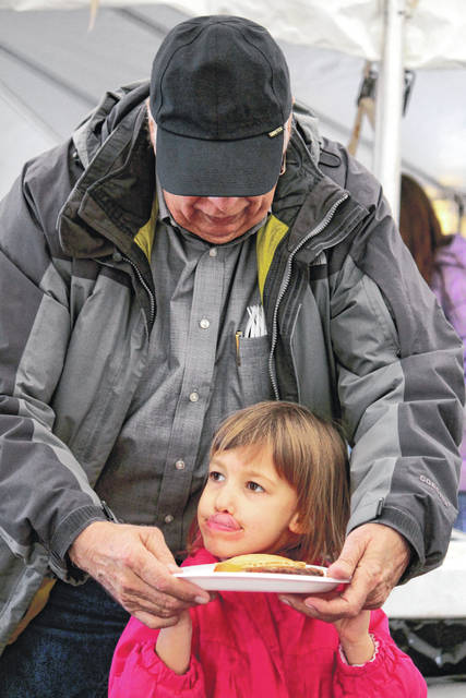 Anna Bolton | Greene County News Sadie Grunow, 4, led by her grandfather, Ed Cohrs, carries her plate stacked with pancakes at Greene County Parks & Trails' (GCP&T) Pancakes in the Park March 2 at Russ Nature Reserve.