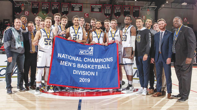Members of the Cedarville University men's basketball team hold the championship banner after winning the NCCAA national title game, March 16 in Winona Lake, Indiana.
