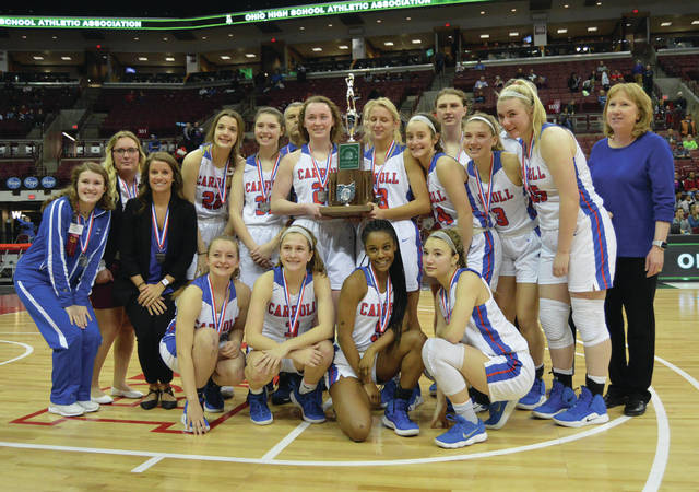 Members of the 2018-'19 Carroll High School girls basketball team pose with the Division II state championship runner-up trophy, after Saturday's March 16 loss to Toledo Rogers, at the Jerome Schottenstein Center, in Columbus.