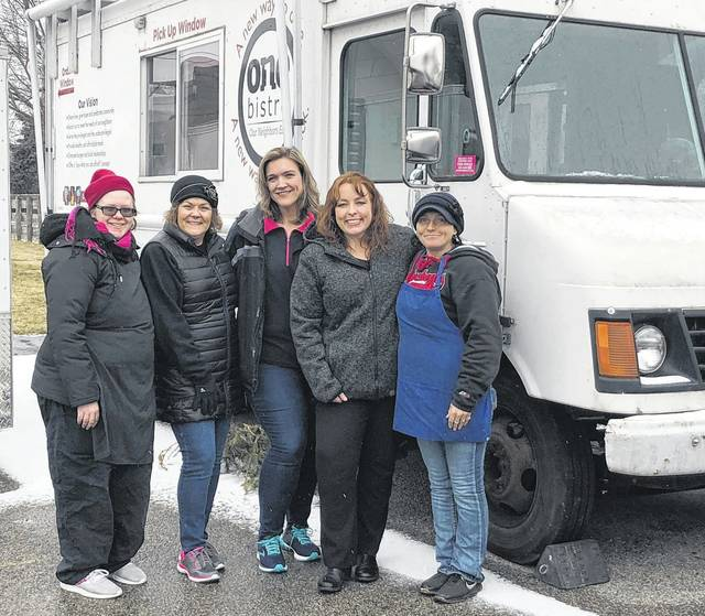 Scott Halasz | Greene County News Bourbon Bayou Bistro owner Jennifer (far right) along with her support system of Denise Davis from One Bistro, and customers Melissa Walters and Liz Dillon, pose in front of the One Bistro food truck. That food truck was sold to Jennifer to help her keep her business on North Detroit Street going.