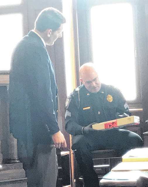 Anna Bolton | Greene County News Assistant Prosecutor David Hayes watches during trial April 23 as Xenia Police Sgt. Matthew Foubert examines an evidence box with a knife inside.