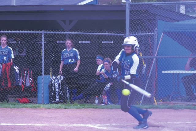 Xenia players look on as Morgan Huffman hits a single to score Caity Moody with the team's second run, in the first inning April 24 against the visiting Kettering Fairmont Firebirds.