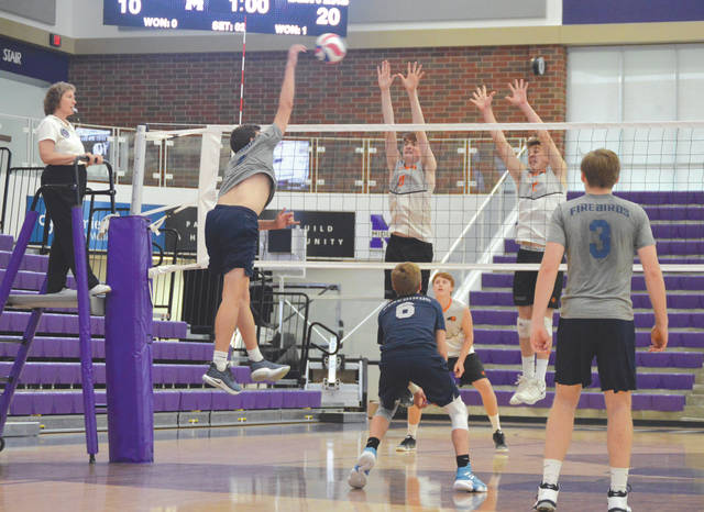 Beavercreek sophomore Sam Little and freshman Josh Culpepper go up to block a shot by a Fairmont outside hitter during the West Regional final, May 25 at Middletown High School.