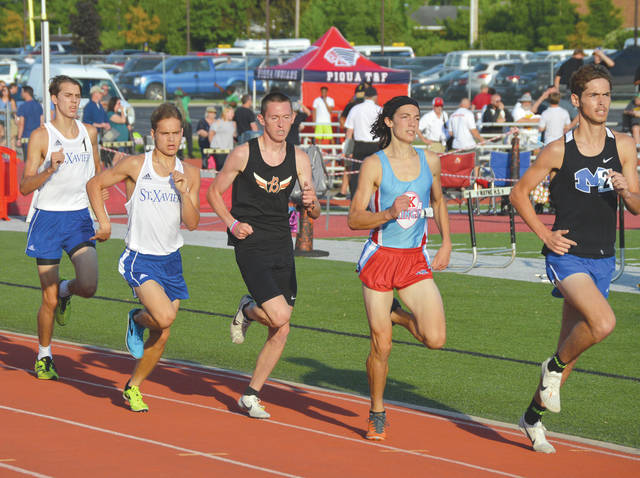 Beavercreek's Riley Buchholz (center) kicked into a new-found gear on the final turn to win Friday's Division I boys 1,600-meter run, at the Regional Track & Field Championships in Huber Heights.