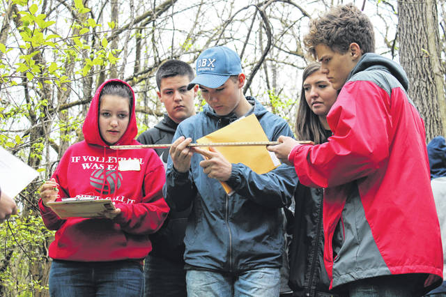 Anna Bolton | Greene County News Cedarville High School students Karie Yake (junior), Hunter Danik (sophomore), Wes Wickline (junior), Anna Winter (junior) and Daniel Ormsbee (sophomore) calculate a measurement of a tree April 30 at Caesar Ford Park during the forestry section of the 2019 Area IV Envirothon.