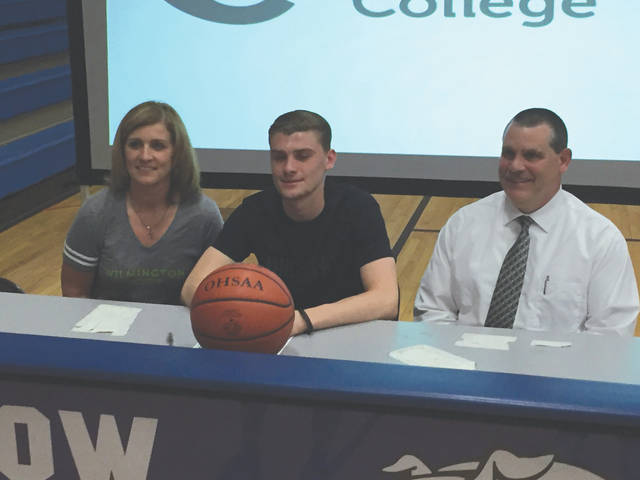 Yellow Springs senior Andrew Clark (center) poses with a basketball with his mother, Tracy Clark and father Mitch Clark, May 22 in the YSHS gymnasium.
