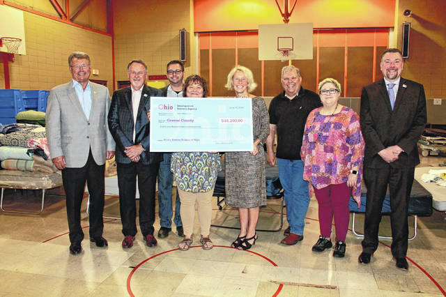 Anna Bolton | Greene County News Greene County commissioners Tom Koogler and Dick Gould, Bridges of Hope board member Nick Seitz, BOH Board President Marlene Labig, Mary Oakley from Ohio Development Services Agency, BOH board members Mike Deis and Kim Osburn, and Director of Department of Development Paul Newman Jr. gather together June 10 for the presentation of funds to benefit the emergency shelter.