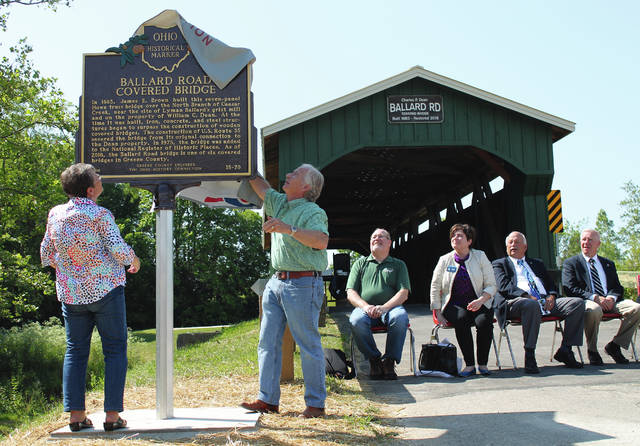 Anna Bolton | Greene County News Greene County Engineer Bob Geyer and Peggy Dean, wife of the late Charles F. Dean, remove the cover from the Ballard Road Covered Bridge's historical plaque June 9, 2017 at the dedication ceremony in New Jasper Township. The original Howe Truss bridge, built in 1883, was the final historic covered bridge Geyer restored.