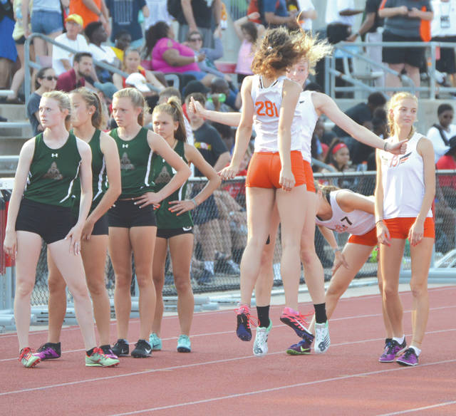 Beavercreek mile relay team members Ashtyn Gluck and Abigail Hobbs leap up for a chest bump as part of their pre-race ritual, June 1 at the state track and field meet in Columbus.