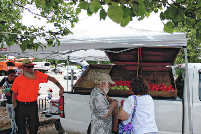 Anna Bolton | Greene County News J.R. Sutherlin and Dan Waters help as shoppers pick out red tomatoes at the Farm to Table Produce truck June 27. The truck visits the Xenia Rural King parking lot Tuesdays and Thursdays, noon to 6 p.m. or until sold out. Also on the truck this time: zucchini, yellow squash, green beans, eggplant, new potatoes, cucumbers, onions, watermelons, blueberries, jellies and berry butter, plus Michelle Wilcox's baked goods like gluten-free pumpkin bread.