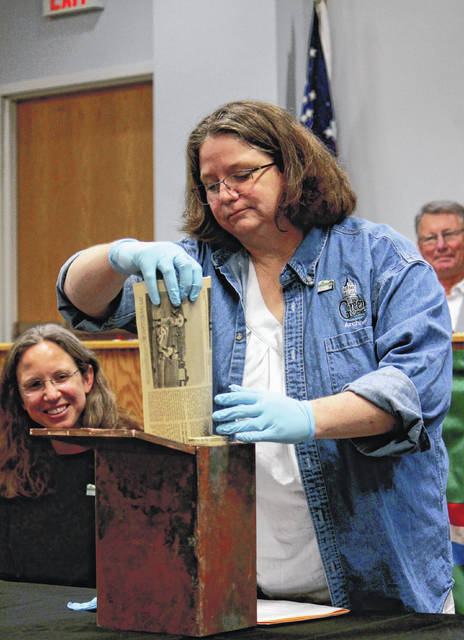 Photos by Anna Bolton | Greene County News Greene County Archivist Robin Heise pulls out the first item, 1969 newspapers, from the copper time capsule.