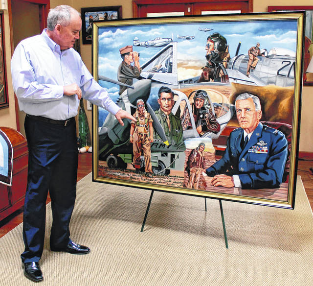 Anna Bolton | Greene County News Mark Bass points out an image of his dad, Lt. Bernie Bass, in a collage portrait painted by Gary Blevins. The specific scene shows the pilot at Philadelphia Municipal Airport in June 1942 prior to his deployment for North Africa.