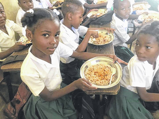 Students at the Becky DeWine School in Cité Soleil, Haiti eat a meal of rice and beans.