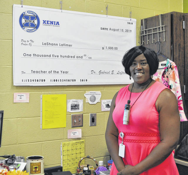 Scott Halasz | Greene County News Cox Elementary School teacher LaShann Latimer shows off the $1,500 check she received for being named the district's 2019 teacher of the year.